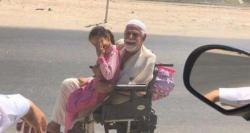 سعودی عرب میں معذور باپ کی بیٹی کو وہیل چیئر پر سکول لے جانے کی تصویر وائرل